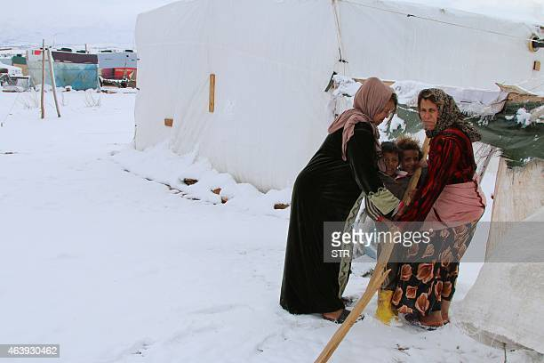 Syrian refugees stand in a makeshift camp covered in snow on February 20 2015 on the outskirts of the Lebanese town of Baalbek Blizzards dumped a...