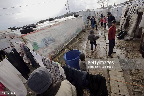 Syrian refugees stand in a refugee camp damaged by a winter storm in Akkara remote province of north Lebanon on January 7 2015 Heavy snowfall also...