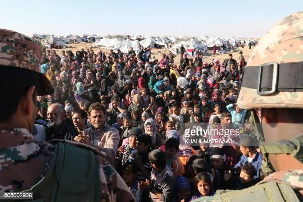 TOPSHOT Syrian refugees stuck between the Jordanian and Syrian borders wait to cross into Jordan at the Hadalat border crossing east of the Jordanian...