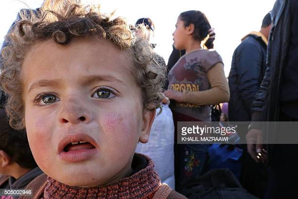 Syrian refugees stuck between the Jordanian and Syrian borders wait to cross into Jordan at the Hadalat border crossing east of the Jordanian capital...