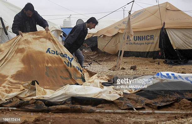 Syrian refugees try to repair damaged tents following heavy rain at the Zaatari refugee camp near the Syrian border with Jordan in Mafraq on January...