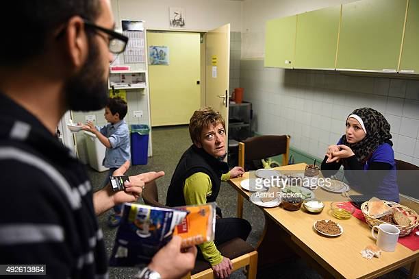 Syrian refugees Wael AlAwis left his wife Reem Haskour right and their son Ali AlAwis have breakfast with church member Ilona BŸnning at the...
