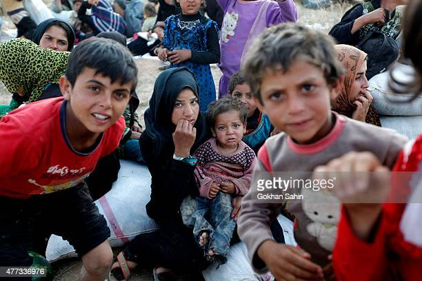 Syrian refugees wait after crossing into Turkey at the Akcakale border gate on June 16 in Sanliurfa province Turkey Kurdish fighters in Syria have...