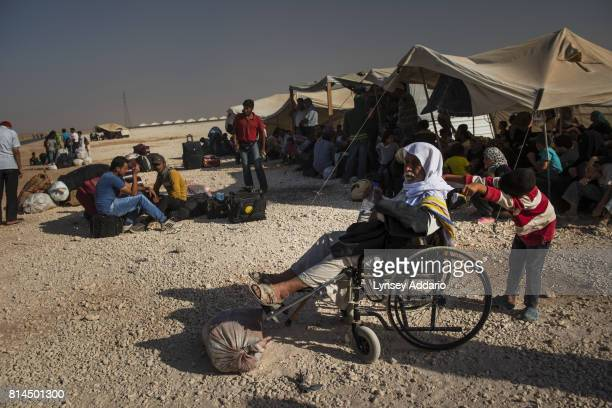 Syrian refugees wait for buses to take them back to the border to cross back into Syria from their current location in Zaatari camp in Jordan...