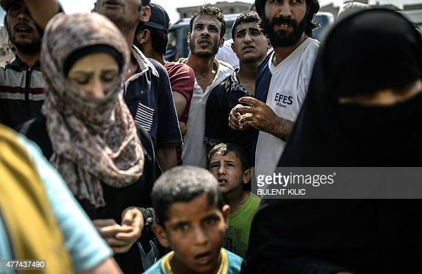 Syrian refugees wait for supply near the Turkish border post of Akcakale province of Sanliurfa on June 17 2015 The first Syrian refugees returned to...
