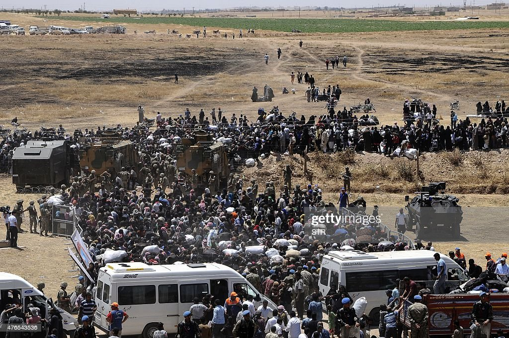 Syrian refugees wait for transportation after crossing into Turkey from the Syrian town of Tal Abyad, near Akcakale in Sanliurfa province, on June 10, 2015. More than 2,000 refugees crossed from Syria into Turkey on Wednesday, fleeing clashes pitting Kurdish fighters against the Islamic State (IS) group, according a Turkish official. They left their war-torn country via the Turkish border post of Akcakale, which faces the IS-held Syrian town of Tel Abyad.