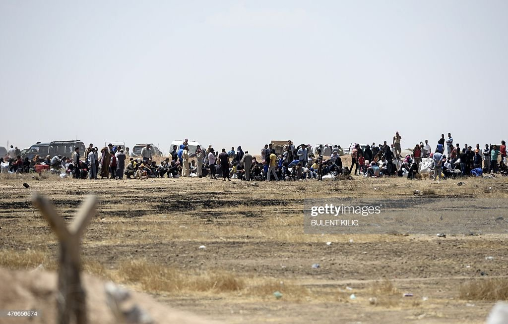 Syrian refugees wait near the Turkish border in Akcakale in the Sanliurfa province not far from the Syrian town of Tal Abyad on June 11, 2015. More than 2,000 refugees have crossed from Syria into Turkey, fleeing clashes pitting Kurdish fighters against the Islamic State (IS) group, a Turkish official said. They left their war-torn country via the Turkish border post of Akcakale, which faces the IS-held Syrian town of Tel Abyad, the official said.