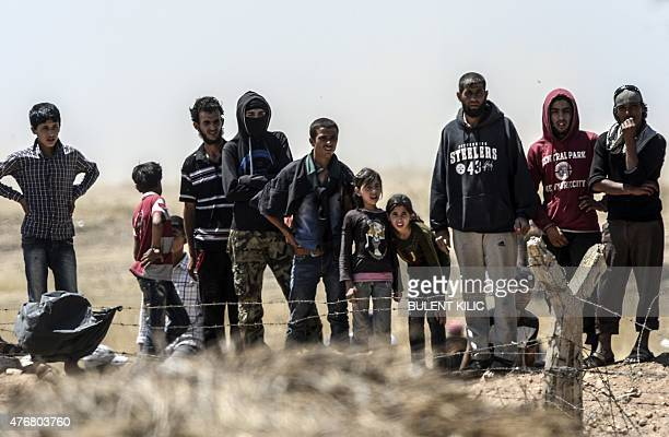 Syrian refugees wait near the Turkish border in Akcakale in the Sanliurfa province not far from the Syrian border town of Tal Abyad on June 12 2015...