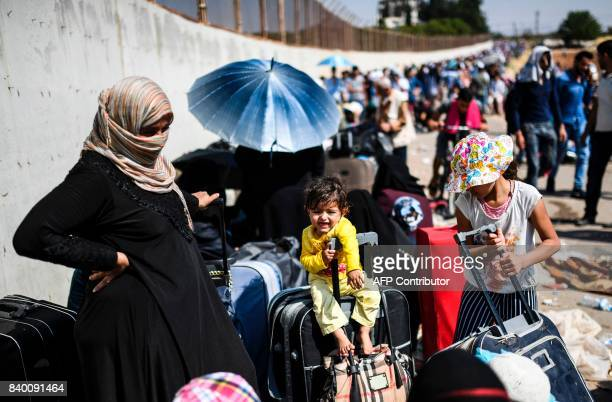 TOPSHOT Syrian refugees wait on August 28 2017 at the Oncupinar crossing gate close to the town of Kilis south central Turkey as they wait to cross...