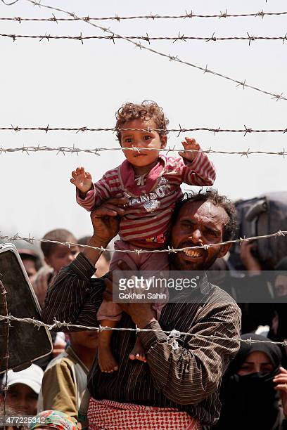 Syrian refugees wait on the Syrian side of the border to cross Akcakale on June 15 2015 in Sanliurfa province southeastern Turkey Thousands of...