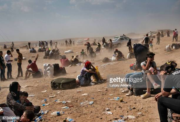 Syrian refugees wait to be transported to a refugee hours after crossing into northern Iraq near the Peshkhabour border point in Dahuk Northern Iraq...