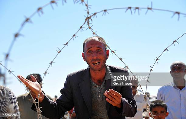 Syrian refugees wait to cross into Turkey at the border September 22, 2014 near the southeastern town of Suruc in Sanliurfa province, Turkey. The...