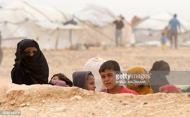 Syrian refugees wait to cross to the Jordanian side of the Hadalat border crossing a military zone east of the capital Amman after arriving from...