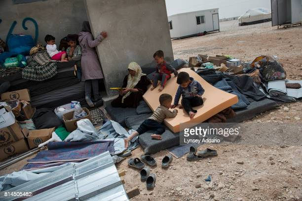 Syrian refugees wait with their belongings to be alotted a trailer by the United Nations High Commission for Refugees after living in a tent for...