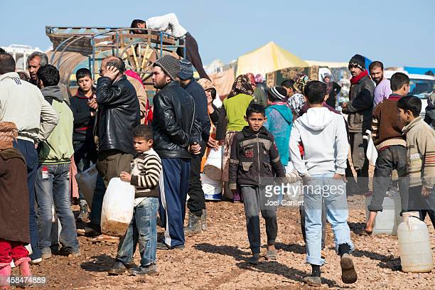 syrian refugees waiting for water at idp camp - refugee camp stock pictures, royalty-free photos & images