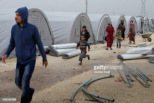 Syrian refugees walk in a refugee camp after crossing from Syria into Turkey in Suruc September 28 2014 south of Sanliurfa Turkey Islamic State...