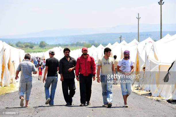 Syrian refugees walk on June 18 2011 in the Boynuyogun Turkish Red Crescent camp in the Altinozu district of Hatay near the Syrian border Some 10000...