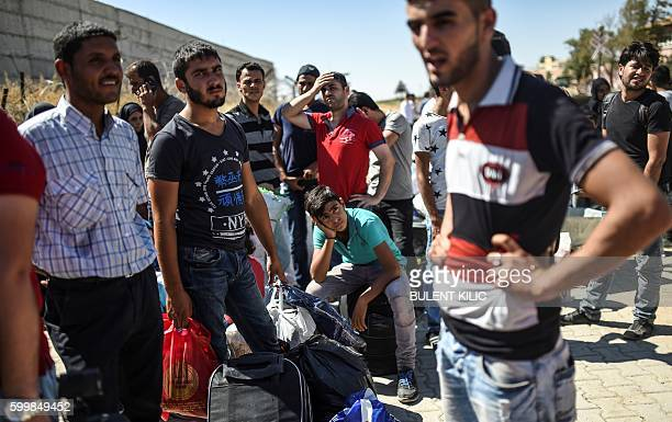Syrian refugees walk on their way back to the Syrian city of Jarabulus on September 7 2016 at Karkamis crossing gate in the southern region of Kilis...