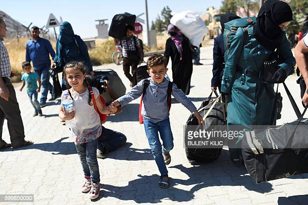 TOPSHOT Syrian refugees walk on their way back to the Syrian city of Jarabulus on September 7 2016 at Karkamis crossing gate in the southern region...
