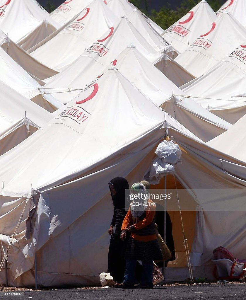 Syrian refugees walk past tents at a cam & Syrian refugees walk past tents at a cam Pictures | Getty Images