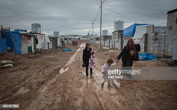 Syrian refugees walk through the mud at the Qushtapa Refugee Camp on December 14 2014 in Erbil Iraq Although the autonomous Kurdistan region of...