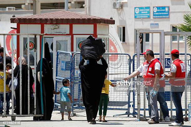 Syrian refugees walk with their belongings to cross back to the Syrian border town of Tal Abyad from Turkey at the border crossing in Akcakale...