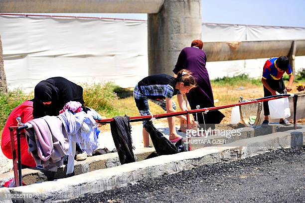 Syrian refugees wash their clothes on June 18 2011 at the Boynuyogun Turkish Red Crescent camp in the Altinozu district of Hatay near the Syrian...