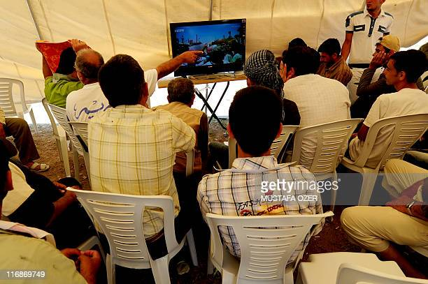 Syrian refugees watch news about their country on the United Arab Emirates' Orient News channel in a tent on June 18 2011 in the Boynuyogun Turkish...