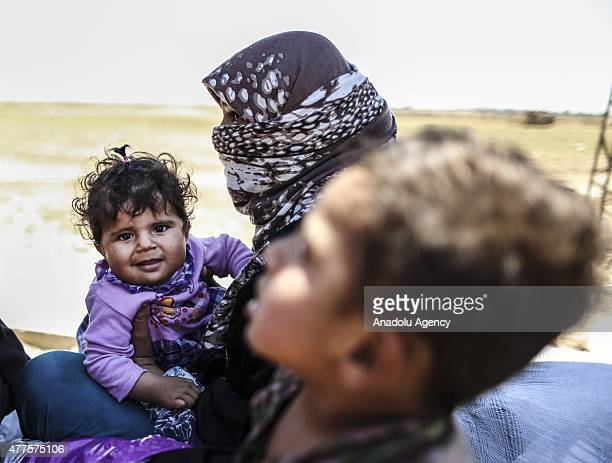Syrian refugees who fled clashes in the Syrian town of Tal Abyad wait at Akcakale Border gate to return their country as the gate on the other side...