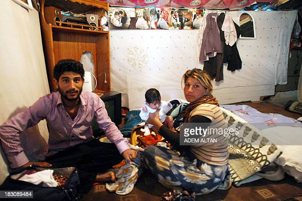 Syrian refugees who flock by dozens in Turkey each day fleeing the civil war in their country sit on October 4 2013 at a makeshift camp in Ankara...