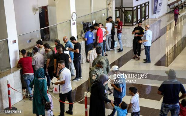 Syrian refugees who were suddenly deported from Turkey queue up to register with officials at the Bab alHawa crossing between Turkey and Syria's...
