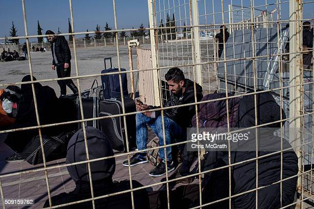 Syrian refugees wishing to return to Syria wait for transport to arrive as a small number of Syrian refugees were allowed to return to Syria at the...