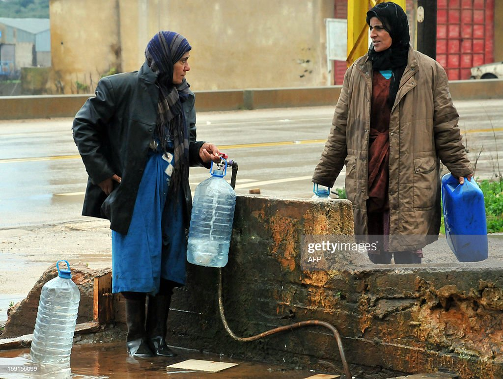 Syrian refugees women fill containers with clean water in the village of Kfarkahel, in the Koura district close to the northern city of Tripoli, on January 9, 2013, as stormy weather sparked widespread flooding, prompting chaos on the roads and a nationwide school closure. The number of Syrian refugees in Lebanon is already totalling 156,000, according to UN figures, and 200,000 according to the Lebanese government estimates. AFP PHOTO/Ibrahim Chalhoub