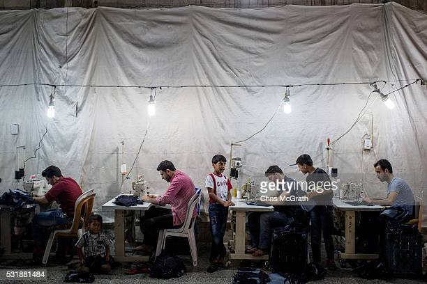 Syrian refugees work in a Syrian owned clothing factory on May 17 2016 in Gaziantep Turkey Since fleeing the war and after the new EU Turkey deal...