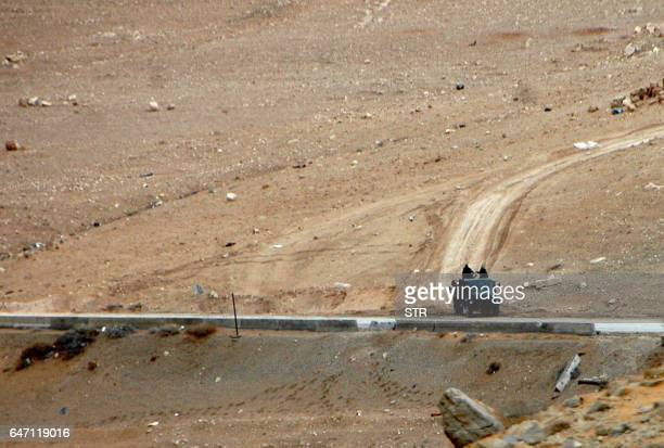 Syrian regime fighters take position as they advance to retake the ancient city of Palmyra from Islamic State group fighters on March 2 2017 PHOTO /...