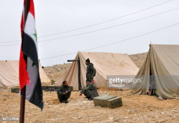 Syrian regime fighters take position as they advance to retake the ancient city of Palmyra, from Islamic State group fighters on March 2, 2017. / AFP...