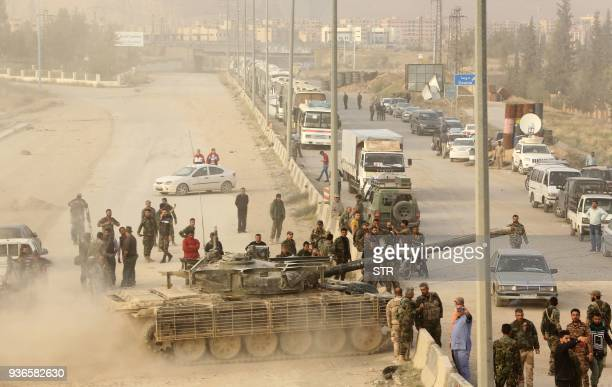 TOPSHOT Syrian regime forces gather near buses waiting at the entrance of Harasta in Eastern Ghouta on the outskirts of Damascus on March 22 after a...