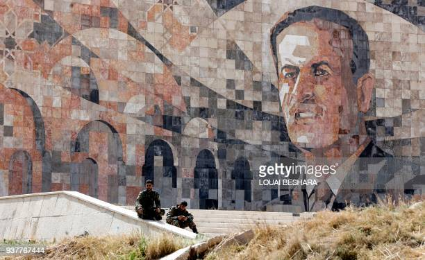 TOPSHOT Syrian regime forces sit by a marble mosaic monument depicting a picture of late President Hafez alAssad at the entrance of Harasta in...