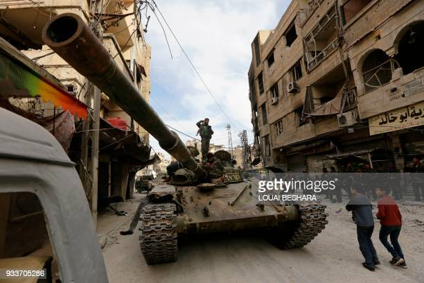 TOPSHOT Syrian regime forces stand on a tank in the Eastern Ghouta town of Saqba after they took control of the southern pocket held by the Faylaq...