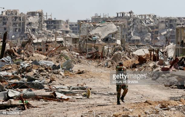 Syrian regime member walks amid the destruction in Jobar in Eastern Ghouta on the outskirts of the capital Damascus on April 2 2018 Syria's regime...