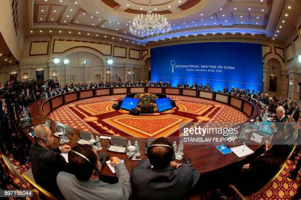 Syrian regime representatives and opposition delegates along with other attendees take part in the session of Syria peace talks in Astana on December...