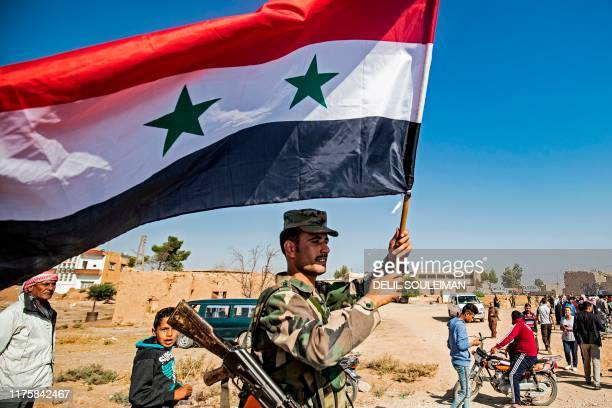 Syrian regime soldier waves the national flag a street on the western entrance of the town of Tal Tamr in the countryside of Syria's northeastern...