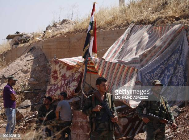 Syrian regime soldiers at a checkpoint watch Syrian rebels during evacuation from Daraa city, on July 15 as Syrian government forces heavily bombed...