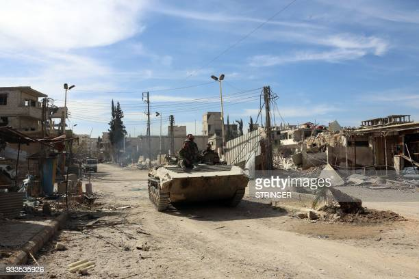 TOPSHOT Syrian regime soldiers drive through the town of Kafr Batna in Eastern Ghouta on March 18 2018 Regime forces have retaken some 80 percent of...