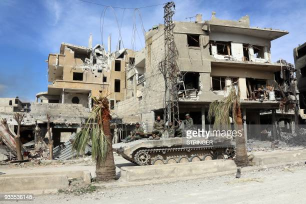 Syrian regime soldiers drive through the town of Kafr Batna in Eastern Ghouta on March 18 2018 Regime forces have retaken some 80 percent of Eastern...