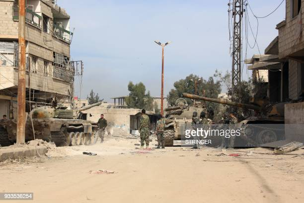 Syrian regime soldiers gather in the town of Kafr Batna in Eastern Ghouta on March 18 2018 Regime forces have retaken some 80 percent of Eastern...