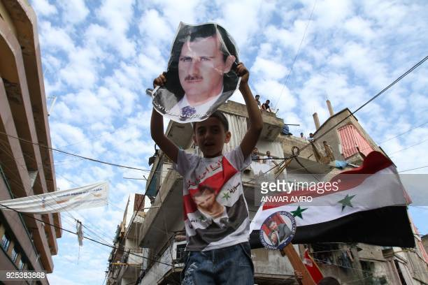 Syrian regime supporters carry pictures of President Bashar alAssad during a protest in the Nabaa neighborhood of Beirut on October 2 as Syrian...