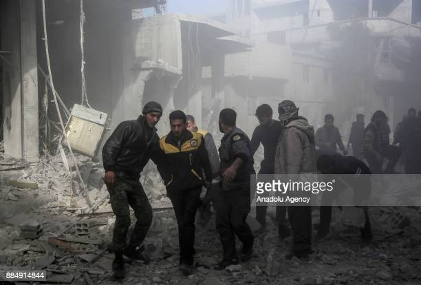 Syrian rescue teams carry a wounded person following the Assad regime's air strikes over residential areas in the deescalation zone in the Eastern...