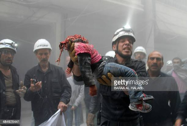 Syrian rescue worker carries the beheaded body of a child after reported air strikes by government forces in the Aleppo district of Ansari in the...