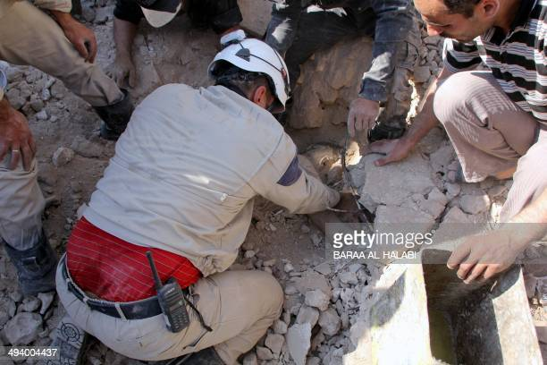 A Syrian rescue worker removes a body lying buried under the rubble on May 27 2014 following a reported air strike by government forces in the...